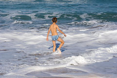 Child and sea. Child having a bath in rough water, at Liencres beach, Cantabria, Spain Stock Photography