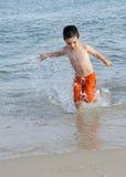 Child in sea on beach Stock Photos