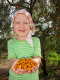The child with sea-buckthorn berries Stock Photography