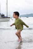 Child at sea port. Child boy playing in the sea, running in a shallow water in a  port or harbour, a yacht in the background; St. Ives, Cornwall, England, UK Royalty Free Stock Images