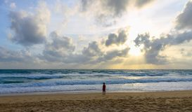 Child by the sea at sunset looks at the waves. Child on the beach looking at the sea at sunset Stock Photography