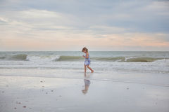 Child searching for seashells. Child walking along the beach at sunset searching for seashells and treasure Stock Image