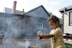 Child seasoning pork chops with pepper Stock Images