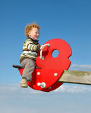 Child on See Saw. Happy little Boy having fun high up a seesaw, against a blue sky, no horizon Stock Photos