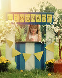 Child Selling Lemonade at Stand Outside. A little girl has an outdoor homemade lemonade stand with a sign and she looks happy for a small business or money royalty free stock images
