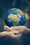 Child and senior holding Earth planet in hands Stock Photos