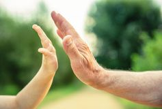 Child and senior man hands giving five in the Royalty Free Stock Photography