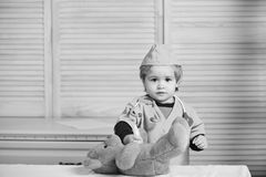 Child with serious face playing doctor. Medical education and childhood concept. Kid in doctor coat. Makes injection to teddy bear. Boy in surgical uniform royalty free stock photo