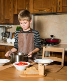 Child serving Borshch, traditional Russian and Ukrainian soup. Pouring soup into a plate with ladle from pan in kitchen. Royalty Free Stock Images