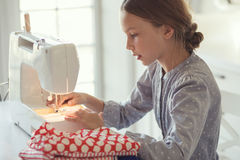 Child sewing. 9 years old child studying work with sewing machine stock photography