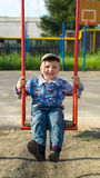 The child shakes on a swing Royalty Free Stock Images
