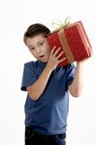 Child shaking a wrapped present. A young boy wearing jeans and t-shirt shakes a present to determine the contents Royalty Free Stock Image