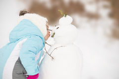 Child sharing affection to a snow man Royalty Free Stock Images