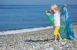 Child with shawl goes on pebble beach. Summer Stock Photos