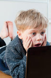 Child shocked by web page content. Little boy shocked whilst browsing the internet on his laptop Royalty Free Stock Photo