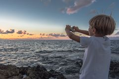 Shooting the sunset. A Child shooting the sunset stock photography
