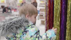 The child in the shop looking at the goods. Sale of toys and Christmas trees until xmas. Christmas gifts for loved ones. Christmas gifts for loved ones stock video