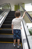 Child in shopping center standing on moving escalator. Royalty Free Stock Images