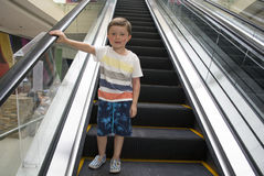 Child in shopping center standing on moving escalator. Stock Photo