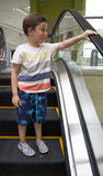 Child in shopping center standing on moving escalator Royalty Free Stock Photography
