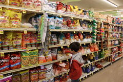 Child shopping in supermarket. A young Child is shopping for snack Royalty Free Stock Photo