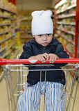 Child in shopping trolley. Bored unhappy child sitting in a shopping trolley in a supermarket Royalty Free Stock Photos