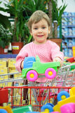 Child in shoppingcart with toy car Royalty Free Stock Photos