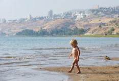 Child on the shore of lake Kinneret in the morning Stock Photography