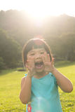 Child shouting in park. Asian child is shouting at park against sunlight Stock Photography