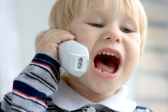 Child shouts on the phone. The child shouts on the phone Stock Images