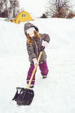 Child is shoveling snow in front of his house. Royalty Free Stock Images