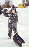 Child is shoveling snow in front of his house. Cleaning of snow after a snowfall Royalty Free Stock Photography
