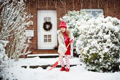 Child shoveling snow. Little girl with spade clearing driveway after winter snowstorm. Kids clear path to house door after. Christmas blizzard. Snowfall fun stock photography
