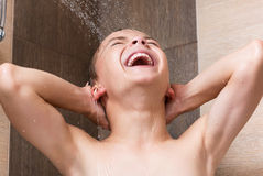 Child in shower. Cheerful boy washing face and body in shower in the bathroom royalty free stock images
