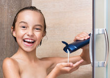 Child in shower. Happy girl washing head in shower in the bathroom royalty free stock photography