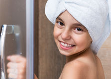 Child in shower. Portrait of girl with towel on head. Girl takes a shower in the bathroom Royalty Free Stock Photo