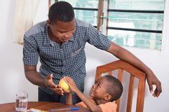 Child showing an apple to his father. This child shows that apple to his father because he wants to eat it Royalty Free Stock Image
