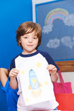 Child showing drawing of rocket in space. On a piece of paper royalty free stock image