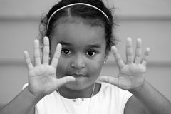 A child showing empty hands. Young small african american girl child showing two empty hands and ten fingers Royalty Free Stock Photography