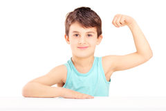 A child showing his muscles seated on a table Stock Image