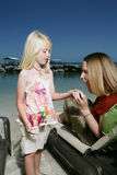Child showing mother shells. A view of a young girl showing her mother a handful of shells picked up on the beach Royalty Free Stock Image