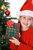Child showing a present by the Christmas tree Stock Images