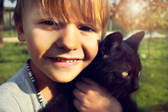 Child shows  with affection his  black cat Royalty Free Stock Photos