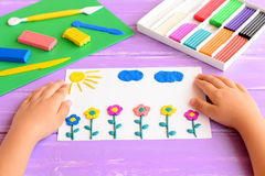 Child shows a card with plasticine flowers, sun and clouds. Supplies for children art crafts on wooden table. Modeling clay craft Stock Photos