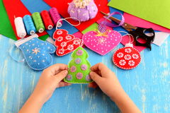 Child shows Christmas crafts. Felt fur-tree, mitten, heart, ball decor Stock Photos