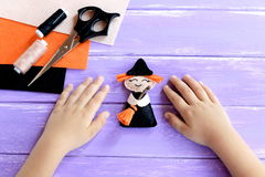 Child shows a Halloween witch doll. Child put his hands on a wooden table. Needlework supplies. Original witch crafts for kids Royalty Free Stock Image