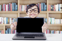 Child shows hand gesture with laptop in library. Happy little girl wearing glasses and smiling on the camera while showing two thumbs up with empty laptop screen Stock Images