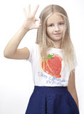 Child shows okay wearing a T-shirt with strawberries Stock Photos