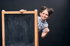 The child shows a sign of approval standing at the school Board. positive schoolgirl peeking out from behind a black school Board royalty free stock photos