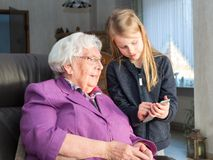 Child shows something interesting on his smartphone to his grand. A 7-year-old kid holding a smartphone shows something funny to his 95-year-old grandmother. She Stock Images